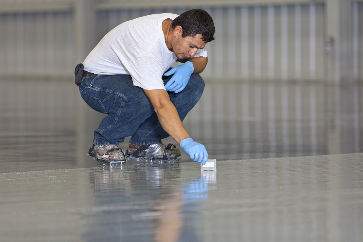 man applying epoxy on a garage floor